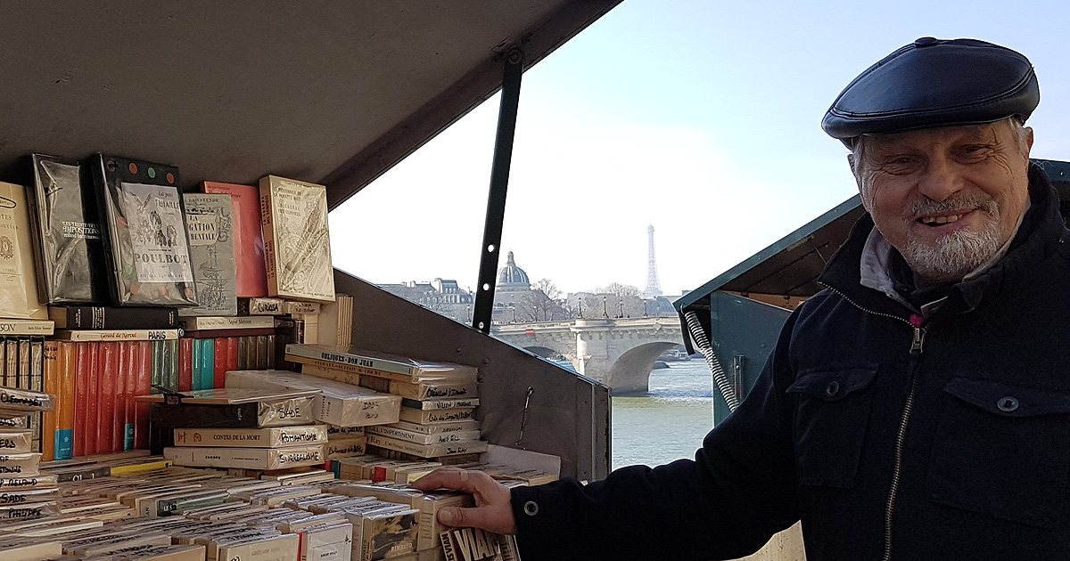 A Paris bouquiniste shows off his books with the Eiffel Tower in the background